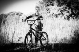 Zwartwit portret van kind / jongen op fiets - Portretshoot - Diana van Neck -Fotograaf Zutphen