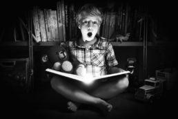 Zwartwit portret van kind die een avontuurlijk boek leest - Portretshoot - Diana van Neck -Fotograaf Zutphen